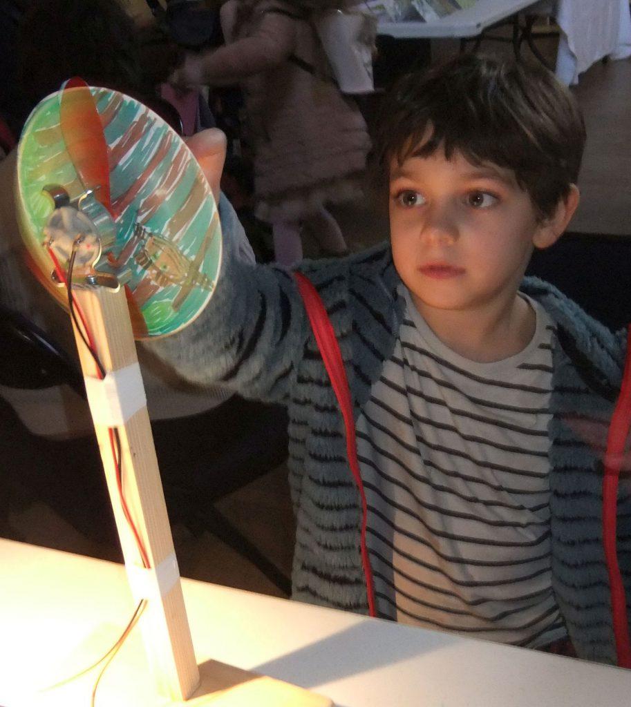 Boy looking at miniature wind turbine
